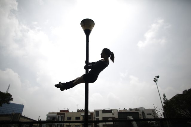 "A woman performs a pole dancing routine on a lamp post during the national day celebration of ""Urban Pole"" dance at a park in Mexico City June 8, 2014. (Photo by Tomas Bravo/Reuters)"