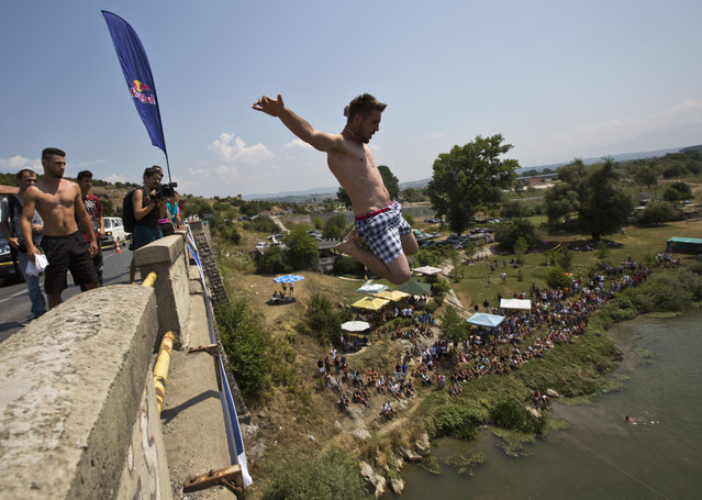 Spectators watch as a diver jumps from the Ura e Shenjte bridge during the traditional annual high diving competition, near the town of Gjakova, 100 kms south of Kosovo capital Pristina, Sunday, July 26, 2015. A total of 27 divers from Kosovo competed diving from a  22 meters high bridge into the Drini i Bardh river. (Photo by Visar Kryeziu/AP Photo)