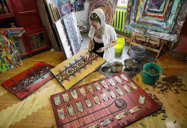 Ukrainian artist Dariya Marchenko works in her studio at pictures which consist of cartridges brought from the frontline in eastern Ukraine, in Kiev, July 22, 2015. (Photo by Gleb Garanich/Reuters)