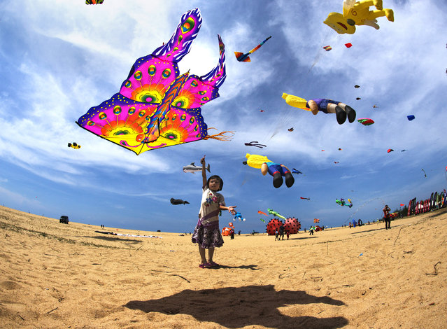 """""""Flying A Kite"""". This image of a little girl flying a kite was shot during The International Kite Festival in Pantai Getting, Kelantan. This event is held yearly in May, and showcases the many different kites by other countries. Photo location: Pantai Geting, Kelantan, Malaysia. (Photo and caption by Ng Yeow Kee/National Geographic Photo Contest)"""