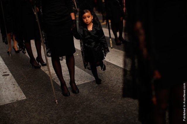"""A girl wearing a traditional mantilla dress takes part in the procession of """"Gitanos"""" brotherhood during Holy Week in the Andalusian city of Malaga, southern Spain"""