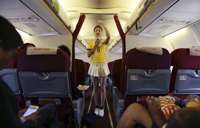 A flight attendant wearing a Brazil soccer team jersey demonstrates the emergency mask on an airplane travelling from Kunming to Hangzhou June 23, 2014. A Chinese airline company renovated the cabin of one of its flights then dressed the flight attendants with soccer jerseys as a way to celebrate the 2014 Brazil World Cup and hoping to attract more customers, local media reported. (Photo by Wong Campion/Reuters)