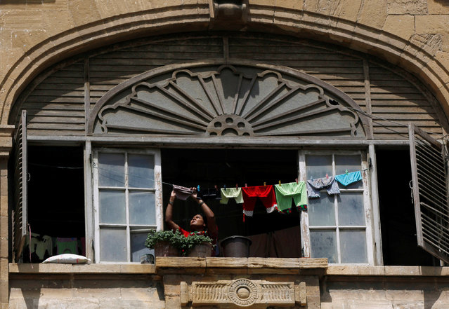 A woman hangs up laundry to dry on a window of a building, built in the British Raj era, in Karachi, Pakistan, May 26, 2016. (Photo by Akhtar Soomro/Reuters)