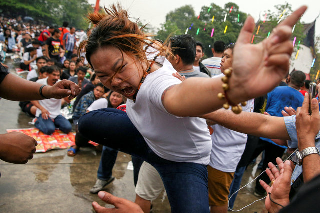 A devotee in trance mimics a beast during a religious tattoo festival at Wat Bang Phra monastery, where devotees believe that their tattoos have mystical powers, in Nakhon Pathom province, Thailand, March 16, 2019. (Photo by Athit Perawongmetha/Reuters)