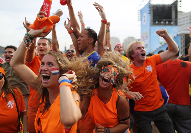 Soccer fans, decked out in orange, the Netherlands' national color, celebrate the second goal scored by Memphis Depay, while watching a live broadcast of the group B World Cup match between Chile and Netherlands, inside the FIFA Fan Fest area on Copacabana beach, in Rio de Janeiro, Brazil, Monday, June 23, 2014. Netherlands won 2-0, taking the top spot in group B. (Photo by Leo Correa/AP Photo)