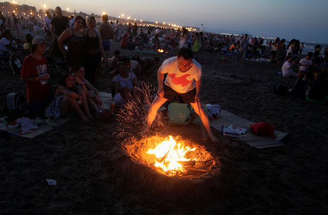 A man tends a bonfire as people gather at the beach to celebrate the summer solstice in Valencia, Spain, June 23, 2017. (Photo by Heino Kalis/Reuters)