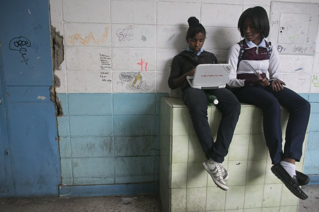 In this May 31, 2016 photo, a student uses a government provided laptop as she and a classmate wait in the hallway for a class to start at their public high school in Caracas, Venezuela. The late President Hugo Chavez made education a centerpiece of his socialist revolution, using the riches from a historic boom in the price of oil to train teachers and distribute free laptops, but in just a few years, all of that progress has been undone. (Photo by Ariana Cubillos/AP Photo)