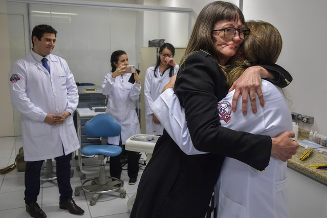 Denise Vicentin (2-R), who lost her right eye and part of her jaw to cancer, embraces a member of the medical staff of doctor Rodrigo Salazar-Gamarra (L) after receiving a digitally-engineered prosthesis, in Sao Paulo, Brazil, on December 3, 2019. Researchers at Paulista University are employing smartphones and 3D printing to create digital facial impressions to make silicone prostheses. The team specializes in maxillofacial prosthetics, a branch of dentistry focused on treating people disfigured by birth defects, disease or trauma. The pioneering method has slashed costs and halved production times. (Photo by Nelson Almeida/AFP Photo)