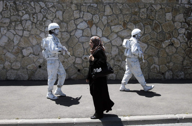 "A woman walks past Israeli artists, one of them Yuda Braun (R), in Jerusalem. Braun says the ""White Soldier"", his artistic project launched in 2009, hopes to add to the discourse on the Israeli-Palestinian conflict"