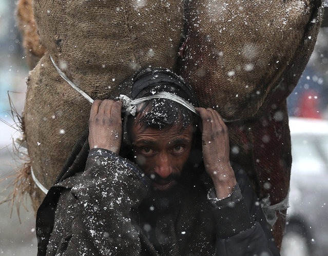 A Kashmiri man carrying sacks of charcoal looks on as it snows in Srinagar, Indian controlled Kashmir, Sunday, January 12, 2020. Kashmir is currently experiencing extreme cold weather. (Photo by Mukhtar Khan/AP Photo)