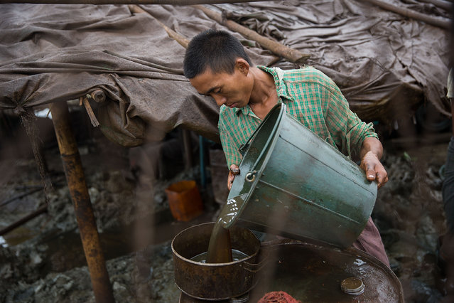 A Burmese worker pours oil into a barrel on August 11, 2015 in Minhla, Burma. Thousands of independent Burmese workers use basic methods to drill in oil fields all over Burma. In Minhla, most workers join crews ranging from 5 to 10 people which use dangerous, generator and pulley methods to extract the oil. (Photo by Taylor Weidman/Getty Images)