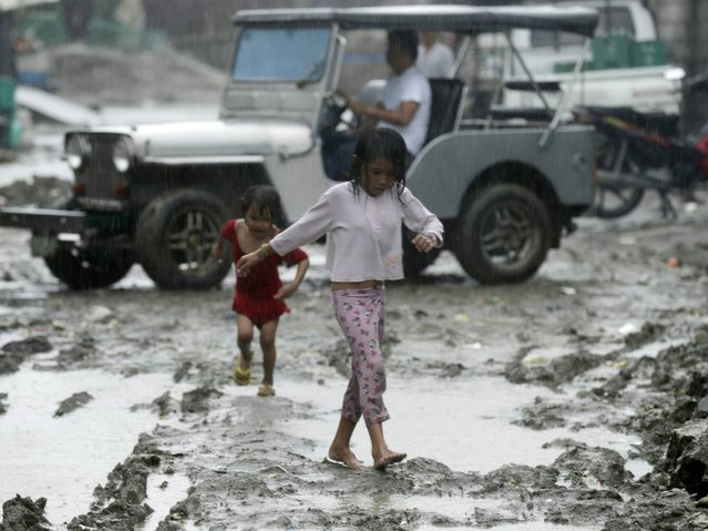 Filipino children wade on a muddy road during a downpour in Navotas city, east of Manila, Philippines, 22 July 2014. State weather forcaster Philippine Atmospheric Geophysical and Astronomical Services Administration (Pagasa) raised storm alert levels as Typhoon Matmo threatened the northern Luzon island and the Calayan-Babuyan-Batanes Group of Islands with heavy rain as it move toward Taiwan and mainland China. (Photo by Francis R. Malasig/EPA)