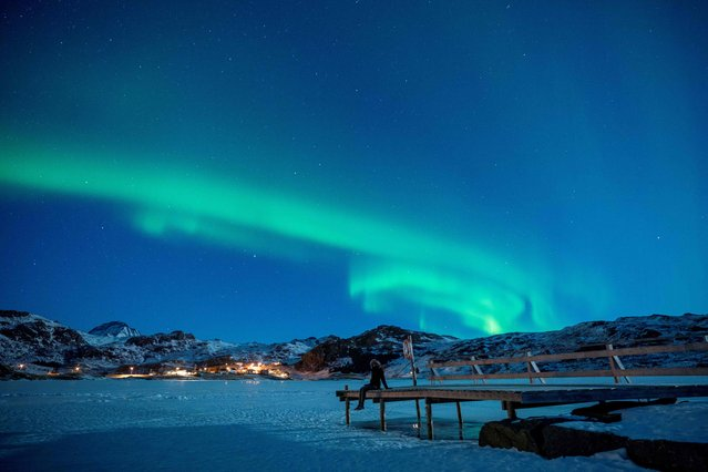 A woman sits on a pier on March 3, 2018 to watch northern lights (Aurora borealis), on the Lofoten Islands, in Bostad, in the arctic circle in northern Norway. (Photo by Olivier Morin/AFP Photo)