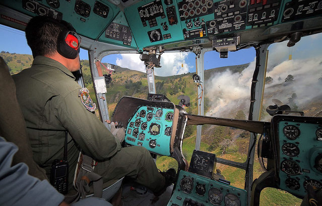 A handout image made available by the Bulgarian Air Force showing a pilot of one of two Mi-17 helicopters of the 24th Airbase Krumovo in Bulgaria approaching the fire area before dropping a load of water onto forest fires raging in the hills near Plovdiv, Bulgaria, 21 August 2015. Bulgarian media report 15 soldiers and two helicopters fought the fires, carrying out 247 approaches and pouring 580 tons of water on the flames. (Photo by EPA/Bulgarian Air Force)