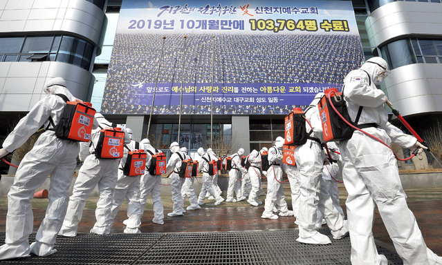 Army soldiers wearing protective suits spray disinfectant to prevent the spread of the coronavirus in front of a branch of the Shincheonji Church of Jesus in Daegu, South Korea, Sunday, March 1, 2020. The coronavirus number of cases shot up in Iran, Italy and South Korea and the spreading outbreak shook the global economy. (Photo by Lee Moo-ryul/Newsis via AP Photo)
