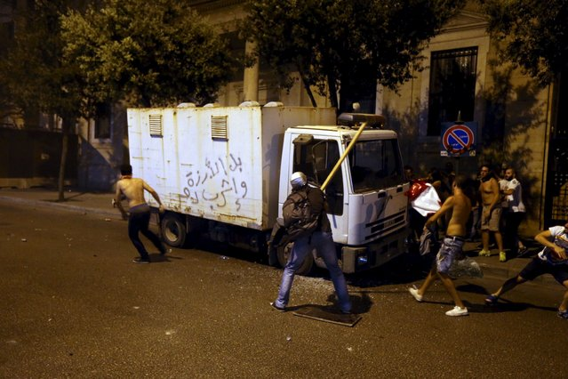 """Protestors run during a protest against corruption and rubbish collection problems near the government palace in Beirut, August 22, 2015. The graffiti on the pick-up truck reads: """"Wet the cedar tree, and drink blood"""". (Photo by Hasan Shaaban/Reuters)"""