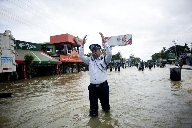 A traffic police officer directs traffic on a flooded street in Bago township, around 100 kilometres (62miles) north of Yangon on August 8, 2014. Heavy downpours in recent days have caused severe flooding in Bago and Mon states. (Photo by Ye Aung Thu/AFP Photo)