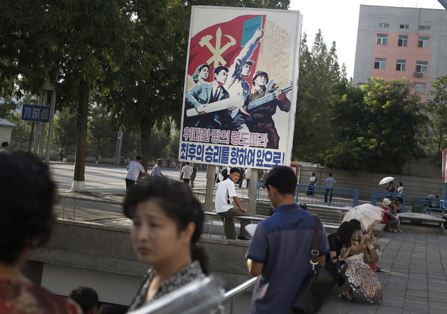 A man sits under a propaganda banner in Pyongyang, North Korea, Sunday, August 23, 2015. North and South Korea on Sunday resumed a second round of talks that temporarily pushed aside vows of imminent war on the peninsula. (Photo by Dita Alangkara/AP Photo)