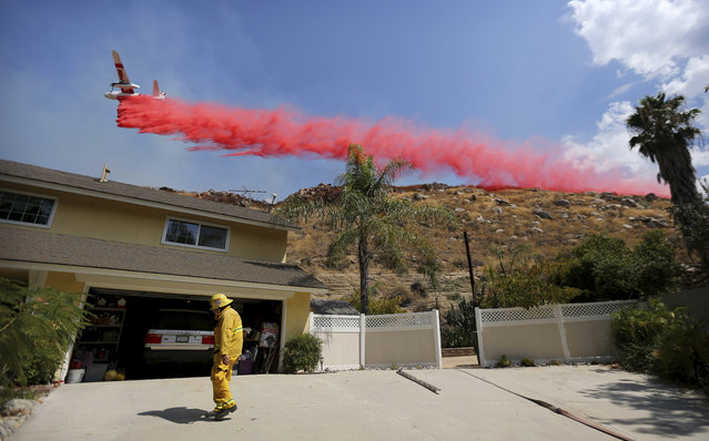 Riverside City Fire Department Engineer Peter Habib stands outside a home to help provide structure protection as a plane drops fire retardant on a hillside during the Marlborough fire on Thursday, August 31, 2017 in Riverside. (Photo by Stan Lim/The Press-Enterprise via AP Photo)