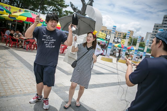 A South Korean Pokemon Go fan (L), hurrays as Lee Jeong-hwan (R) and Barbie Lim (C), broadcasting jockeys for Pokemon Go Korea Facebook page, broadcast live the interview on the street on July 15, 2016 in Sokcho, South Korea. (Photo by Jean Chung/Getty Images)