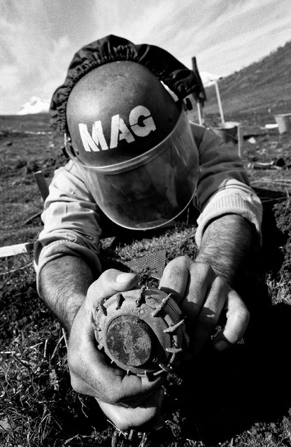 A deminer removing the detonator from the underside of a VS-50 anti-personnel landmine in 2003. (Photo by Sean Sutton for the Mines Advisory Group/The Guardian)