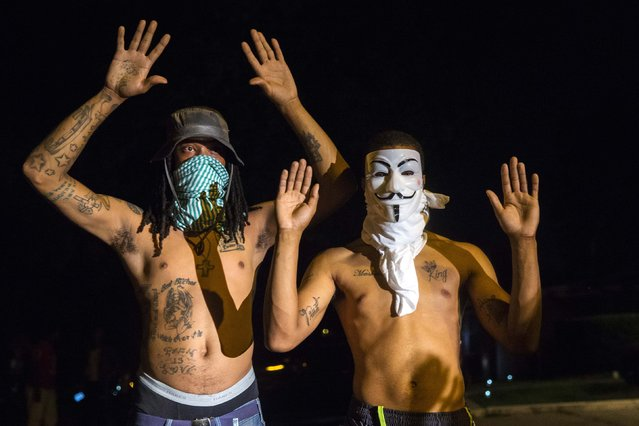 Members of a rowdy group of demonstrators stand with their hands up as they are lit by a police spotlight on West Florissant during protests in reaction to the shooting of Michael Brown near Ferguson, Missouri August 18, 2014. Police fired tear gas and stun grenades at protesters in Ferguson, Missouri on Monday, after days of unrest sparked by the fatal shooting of an unarmed black teenager by a white policeman. (Photo by Lucas Jackson/Reuters)