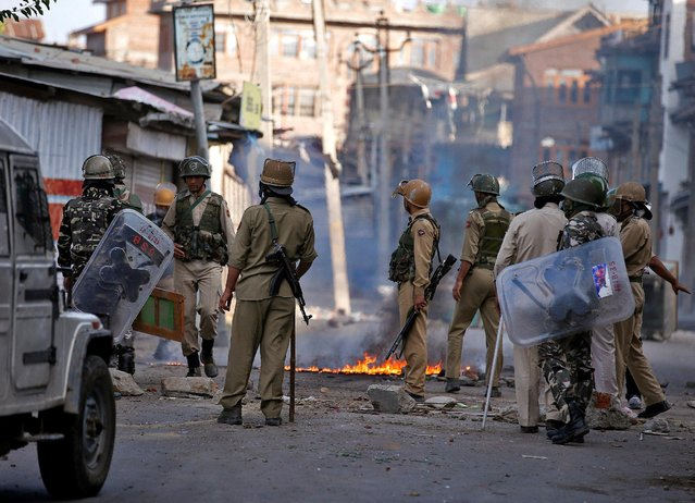 Indian policemen stand next to a burning handcart set on fire by demonstrators during a protest in Srinagar against the recent killings in Kashmir, July 18, 2016. (Photo by Danish Ismail/Reuters)