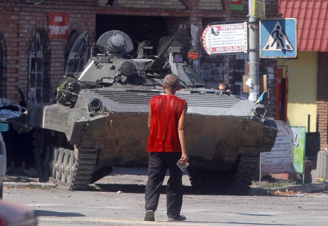 A local resident passes by Ukrainian army APC in the city of Lutugino, eastern Ukraine, Friday, August 15, 2014. Russia let Ukrainian officials inspect an aid convoy while it was still on Russian soil Friday and agreed that the Red Cross can distribute the goods in Ukraine's rebel-held city of Luhansk. (Photo by Sergei Grits/AP Photo)