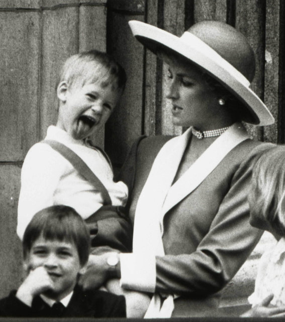 Britain's Princess Diana holds Prince Harry as her older son Prince William (L) looks out over the balcony of Buckingham Palace after attending the Trooping the Colour ceremony in London, June 11, 1988. (Photo by Reuters/Stringer)