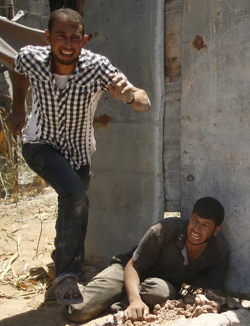 Palestinians react as rescue workers removes the dead body (not pictured) of their relative from under the rubble of a house, which witnesses said was destroyed by an Israeli air strike, in Beit Lahiya in the northern Gaza Strip August 25, 2014. (Photo by Mohammed Salem/Reuters)