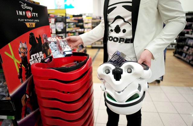 """A shopper uses his Imperial Stormtrooper helmet as a basket after collecting new toys from the upcoming film """"Star Wars: The Force Awakens"""" just after midnight on """"Force Friday"""" in Sydney, September 4, 2015. (Photo by Jason Reed/Reuters)"""
