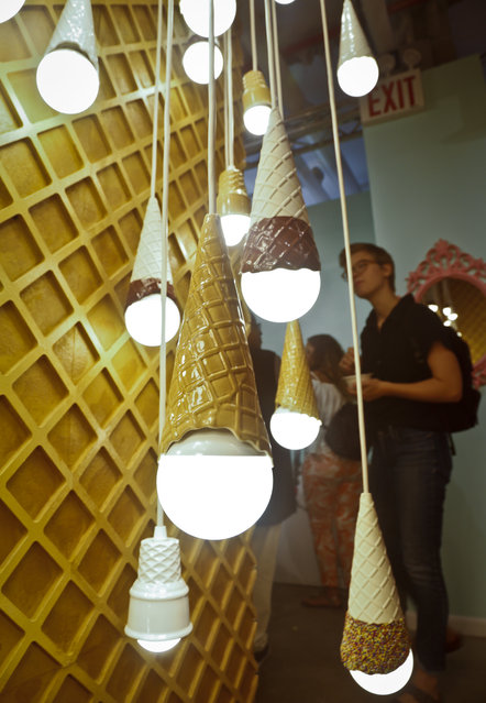A waffle light wall featuring a series of hanging ice cream cones light bulbs is among ice cream-themed works of art previewed at the Museum of Ice Cream, Thursday July 28, 2016, in New York. (Photo by Bebeto Matthews/AP Photo)