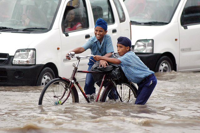 Indian Sikh school children make their way through flood water in a water-logged street after a heavy downpour flooded parts of Amritsar, in India's northwestern state of Punjab, 01 September 2006. (Photo by Narinder Nanu/AFP Photo)