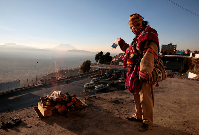 "A Bolivian Aymara witch doctor sprays alcohol to burn an offerings for the ""Pachamama"" (Mother Earth) in El Alto, Bolivia, August 1, 2016. Pachamama is a goddess revered by the indigenous people of the Andes. She is also known as the earth/time mother. In Inca mythology, Pachamama is a fertility goddess who presides over planting and harvesting, embodies the mountains, and causes earthquakes. She is also an ever present and independent deity who has her own self-sufficient and creative power to sustain life on this earth. (Photo by David Mercado/Reuters)"