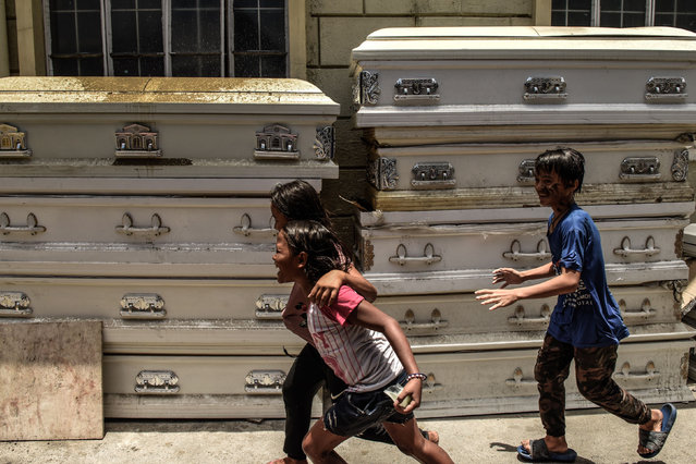 Children run past used caskets at a crematorium facility in Manila on April 29, 2020. Most of the Philippines is under quarantine to contain the spread of the coronavirus that has infected over 7,000 people and killed at least 500 in the country. (Photo by Maria Tan/AFP Photo)