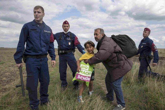 Hungarian policemen attempt to stop a migrant and a child to run from a collection point in Roszke village, Hungary, September 8, 2015. (Photo by Marko Djurica/Reuters)