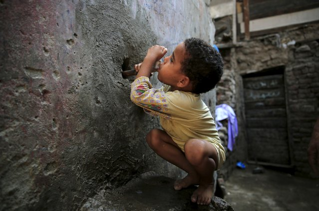 Five-year-old Karkar tries to drink water from a faucet near his home in the Eshash el-Sudan slum in the Dokki neighbourhood of Giza, south of Cairo, Egypt September 2, 2015. (Photo by Amr Abdallah Dalsh/Reuters)