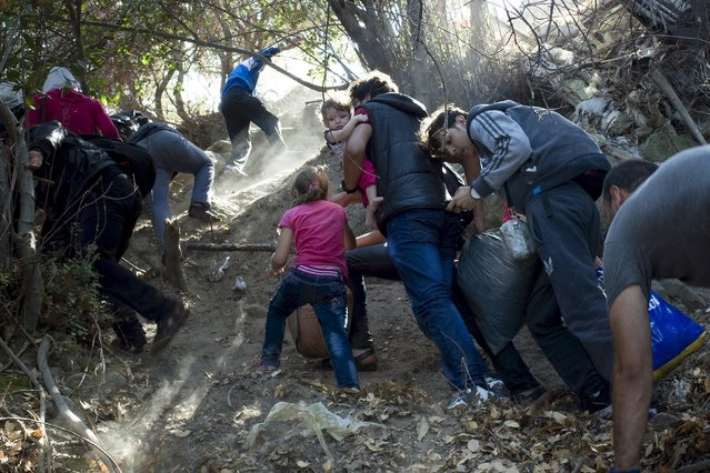 Refugees and migrants climb a slope, moments after arriving on a dinghy, on the Greek island of Lesbos, September 11, 2015. A refugee bottleneck on Greece's easternmost islands has eased after recent dangerous overcrowding, rescue agencies said on Friday, as thousands of migrants per day continue to arrive on the mainland. (Photo by Dimitris Michalakis/Reuters)