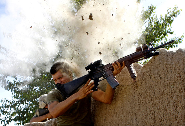 Sgt. William Olas Bee, a U.S. Marine from the 24th Marine Expeditionary Unit, has a close call after Taliban fighters opened fire near Garmsir in Helmand Province of Afghanistan, May 18, 2008. (Photo by Goran Tomasevic/Reuters)