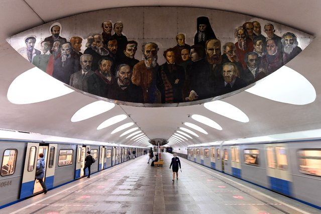 A woman wearing a protective mask walks on a platform at the Otradnoye metro station under an art painting depicting famous Russian writers and composers, in Moscow on May 26, 2020, during a strict lockdown in Russia to stop the spread of the COVID-19 infection caused by the novel coronavirus. Russian President Putin said on May 26 that Russia has passed the peak of coronavirus infections and ordered a postponed World War II victory parade to be held next month. (Photo by Kirill Kudryavtsev/AFP Photo)