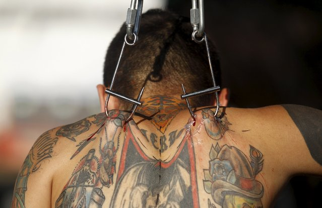 """""""Alias"""" Damian Carnicero is suspended with hooks during the Cali Tattoo Festival in Cali, Colombia, September 12, 2015. (Photo by Jaime Saldarriaga/Reuters)"""