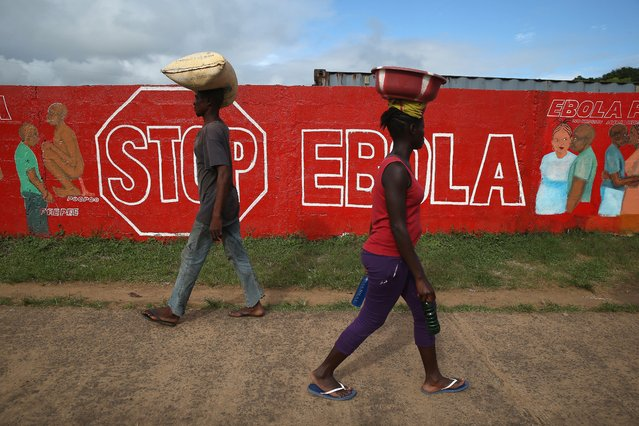 People pass an Ebola awareness mural on October 2, 2014 in Monrovia, Liberia. More than 3,200 people have died in West Africa due to the epidemic. (Photo by John Moore/Getty Images)