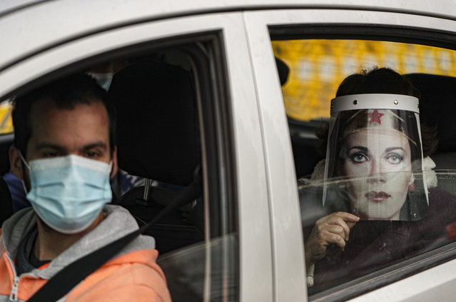 Marisol Aro, wearing a face shield with an image of Wonder Woman, looks out from a car window, amid the new coronavirus pandemic in Santiago, Chile, Saturday, June 27, 2020. Aro's husband bought her the face shield who has since been infected with the new coronavirus and is now intubated in an intensive care unit. (Photo by Esteban Felix/AP Photo)