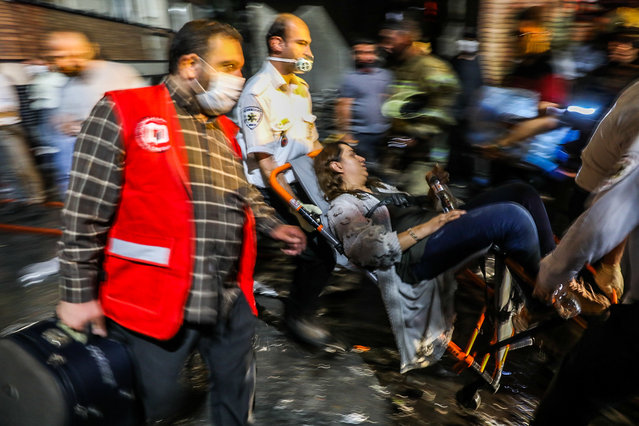 First responders carry away a woman on a wheelchair at the scene of an explosion at the Sina At'har health centre in the north of Iran's capital Tehran northern Tehran on June 30, 2020. The powerful explosion at the clinic in northern Tehran killed over a dozne people, Iran's semi-official ISNA news agency reported, citing the emergency medical services. The blast at Sina At'har health centre caused damage to buildings in the vicinity and sent a plume of thick black smoke into the night sky, state television reported. (Photo by Amir Kholousi/ISNA/AFP Photo)