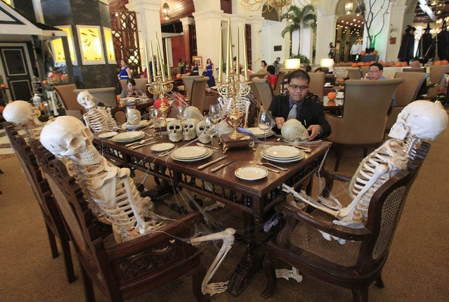 A hotel guest inspects a plastic skull on a dining table as part of the hotel's Halloween display in Manila October 11, 2014. (Photo by Romeo Ranoco/Reuters)