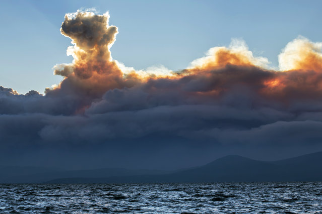 This Wednesday, September 17, 2014 photo shows smoke from a California wildfire rising behind Lake Tahoe as seen from the Nevada side of the lake near Incline Village, Nev. Higher humidity Friday helped slow the growth of the massive Northern California wildfire that authorities say was set deliberately and has forced some 2,800 people to evacuate. (Photo by Steve Ellsworth/AP Photo)
