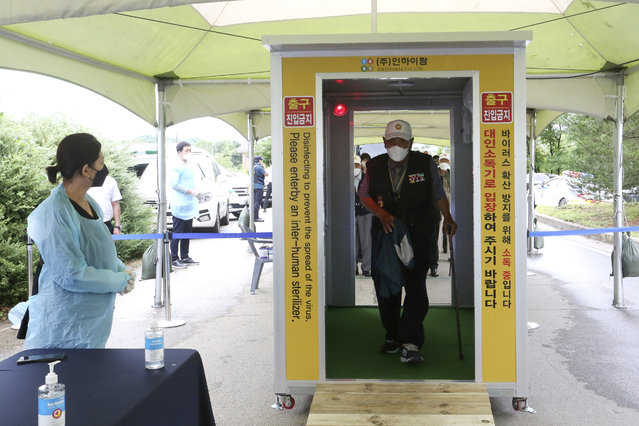 A Koran War veteran walks through a sterilizer as a precaution against the new coronavirus while he arrives to attend a ceremony to mark the 70th anniversary of the outbreak of the Korean War in Cheorwon, near the border with North Korea, South Korea, Thursday, June 25, 2020. (Photo by Ahn Young-joon/AP Photo)