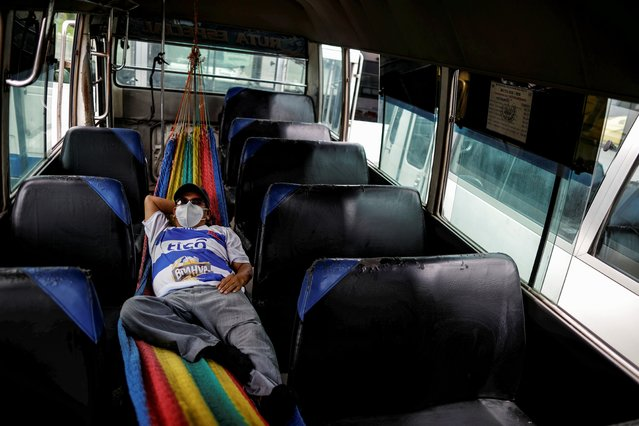 A bus driver rest between trips to transport health workers, after El Salvador's President Nayib Bukele postponed the second phase of economic reopening as the coronavirus disease (COVID-19) outbreak continues, in San Salvador, El Salvador on July 20, 2020. (Photo by Jose Cabezas/Reuters)