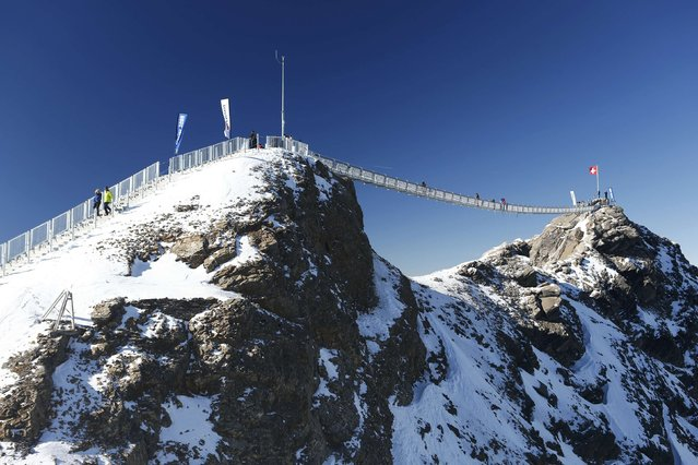 """Guests walk along the """"Peak Walk"""" bridge during a media preview, at the Glacier 3000 in Les Diablerets October 24, 2014. Built between the Scex Rouge and View Point at an altitude of 3,000 metres (9,800 feet) the 107 m (351 feet) long and 80 cm (31 inches) wide hanging bridge is the first in the world to connect two peaks with one another. The Matterhorn, Mont Blanc, Eiger, Moench und Jungfrau mountains can be seen from the platform. (Photo by Denis Balibouse/Reuters)"""