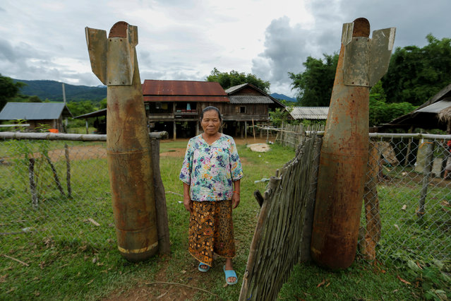 A woman poses at an entrance of her house next to bombs dropped by the U.S. Air Force planes during the Vietnam War, in the village of Ban Napia in Xieng Khouang province, Laos September 3, 2016. (Photo by Jorge Silva/Reuters)